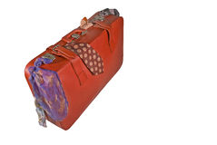 Holiday Suitcase Packed With Clothes. A red suitcase packed and tripping over with colourful clothes on isolated white Royalty Free Stock Photo