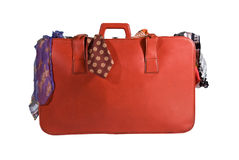 Holiday Suitcase Packed With Clothes. A red suitcase packed and tripping over with colourful clothes on isolated white Royalty Free Stock Images