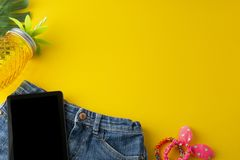 Holiday, summer background. Jeans, palm leaves, tablet screen, pineapple glass juicer. Colorful styled flat lay, yellow background. Holiday, summer background stock image