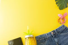 Holiday, summer background. Jeans, palm leaves, tablet screen, pineapple glass juicer. Colorful styled flat lay, yellow background. Holiday, summer background royalty free stock image