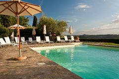 Holiday Swimming Pool. Swimming pool with large umbrellas and sun beds looking out over the hills of Tuscany, Italy Royalty Free Stock Photos