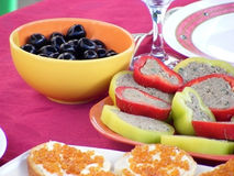Holiday Table. Composition of vegetables, olives and sandwiches on the table in a sunny day Royalty Free Stock Photo