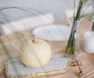 Holiday table decoration with white decorative pumpkins, white plates and candles on wooden background. Flat lay, top view stock photo