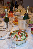 Holiday table with food and wine. Holiday table setting with food and champagne in ice Royalty Free Stock Photography
