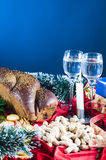 Holiday table setting. With two glass goblets, a loaf of bread, nuts, a lit candle and garland with a blue background Royalty Free Stock Photo