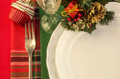 Holiday table setting with Christmas decorations over colorful napkins. Royalty Free Stock Image