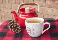 Holiday Teacup and Pot on Throw. Tea in teacup with kettle on winter throw with pinecone stock photography