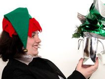 Holiday Teen Girl with Christmas Gift. Teen girl wearing a Christmas elf hat looking happy at a gift bag Royalty Free Stock Image