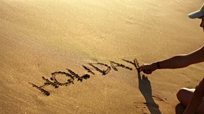 Holiday text in clean sand at summer Royalty Free Stock Photo