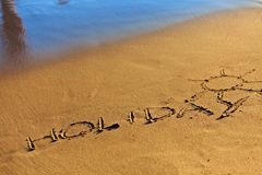 Holiday text written in sand Royalty Free Stock Photo