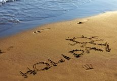 Holiday text written in sand on summer beach. Royalty Free Stock Image