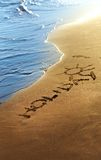 Holiday text written in sand on summer beach. Royalty Free Stock Photography
