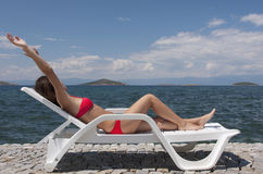 Holiday time. A young woman tanning on a sunbed against a great landscape Stock Photo