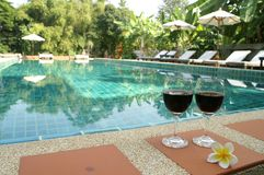 Red wine beside swimming pool. Symbol holiday vocation Stock Images