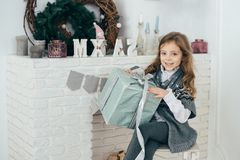 A girl sits at the fireplace and holds a box with a gift in her hands. Holiday time. A girl sits at the fireplace and holds a box with a gift in her hands Royalty Free Stock Photography