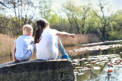 Holiday time relaxing by the water. Two children, older sister and younger brother sitting on the shore of the lake royalty free stock photos