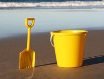 Holiday tools. A yellow plastic bucket and spade on the beach, with the ocean coming in behind them both stock photography