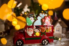 Holiday traditional food bakery. Decorative toy car with christmas Gingerbread cakes in cozy warm decoration with garland lights.  stock image