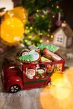 Holiday traditional food bakery. Decorative toy car with christmas Gingerbread cakes in cozy warm decoration with garland lights.  stock photo