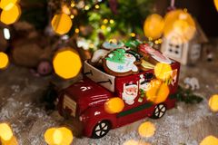 Holiday traditional food bakery. Decorative toy car with christmas Gingerbread cakes in cozy warm decoration with garland lights.  royalty free stock images