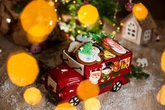 Holiday traditional food bakery. Decorative toy car with christmas Gingerbread cakes in cozy warm decoration with garland lights.  royalty free stock photo
