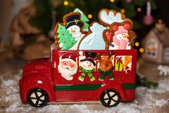 Holiday traditional food bakery. Decorative toy car with christmas Gingerbread cakes in cozy warm decoration with garland lights.  stock photography