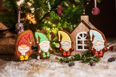 Holiday traditional food bakery. Four Gingerbread little fairytale gnomes in cozy decoration with garland lights.  royalty free stock image