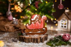 Holiday traditional food bakery. Gingerbread christmas bear in s. Leigh in cozy decoration with garland lights royalty free stock photo