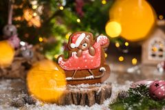 Holiday traditional food bakery. Gingerbread christmas bear in sleigh in cozy decoration with garland lights.  royalty free stock photography