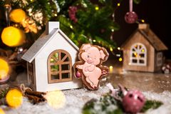 Holiday traditional food bakery. Gingerbread funny piggy in cozy warm decoration with garland lights.  stock photography