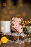 Holiday traditional food bakery. Gingerbread funny pink pig in cozy decoration with garland lights and cup of hot coffee.  stock photography