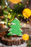 Holiday traditional food bakery. Gingerbread green christmas tree in cozy warm decoration with garland lights royalty free stock photography