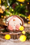 Holiday traditional food bakery. Gingerbread happy sitting Snowman or snowball in cozy warm decoration with garland lights.  stock image