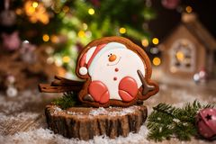 Holiday traditional food bakery. Gingerbread happy sitting Snowman or snowball in cozy warm decoration with garland lights.  stock photography