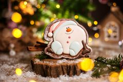 Holiday traditional food bakery. Gingerbread happy sitting Snowman or snowball in cozy warm decoration with garland lights.  royalty free stock image