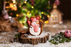 Holiday traditional food bakery. Gingerbread happy snowman in hat and scarf in cozy decoration with garland lights.  stock photography