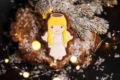 Holiday traditional food bakery. Gingerbread little cute angel girl in cozy decoration with garland lights.  royalty free stock image