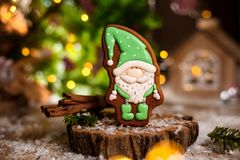 Holiday traditional food bakery. Gingerbread little fairytale gnome in cozy decoration with garland lights stock images