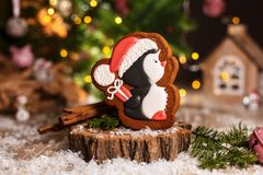 Holiday traditional food bakery. Gingerbread little pinguin in christmas hat with gift in cozy warm decoration with garland lights.  royalty free stock photo