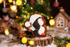 Free Holiday Traditional Food Bakery. Gingerbread Little Pinguin In Christmas Hat With Gift In Cozy Warm Decoration With Garland Lights Stock Image - 134278591