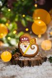Holiday traditional food bakery. Gingerbread old kindly wizard in cozy decoration with garland lights and cup of hot coffee royalty free stock image