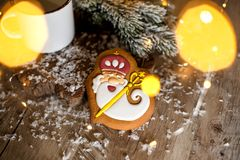Holiday traditional food bakery. Gingerbread old kindly wizard in cozy decoration with garland lights and cup of hot coffee stock images