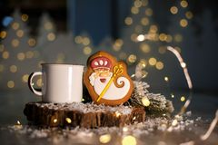 Holiday traditional food bakery. Gingerbread old kindly wizard in cozy decoration with garland lights and cup of hot coffee.  royalty free stock photos