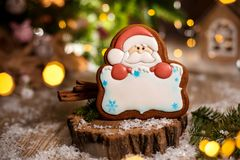 Holiday traditional food bakery. Gingerbread santa claus with copy space in cozy warm decoration with garland lights.  royalty free stock photography