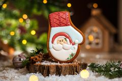 Holiday traditional food bakery. Gingerbread Santa Claus glove in cozy warm decoration with garland lights.  stock image