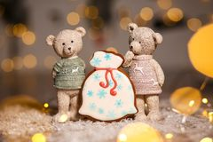 Holiday traditional food bakery. Gingerbread santa`s bag of gifts and two decorative bears in cozy warm decoration with garland. Lights stock photography