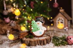Holiday traditional food bakery. Gingerbread snowman with christmas tree in cozy warm decoration with garland lights stock images