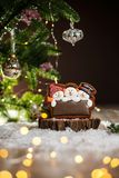 Holiday traditional food bakery. Gingerbread three fun snowmans in cozy warm decoration with garland lights.  royalty free stock photo