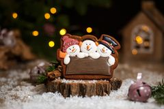 Holiday traditional food bakery. Gingerbread three fun snowmans in cozy warm decoration with garland lights.  royalty free stock photography