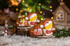 Holiday traditional food bakery. Gingerbread two chirstmas postman and sleigh with gifts in cozy warm decoration with garland. Lights stock photos